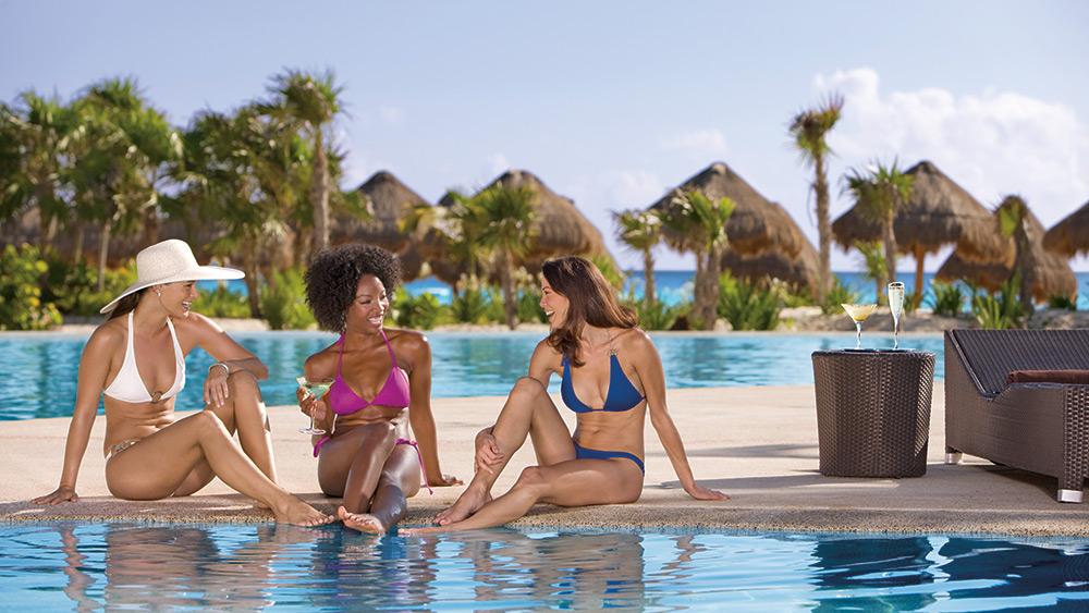 Three women chatting in swimwear on the edge of the pool at Secrets Maroma Beach Riviera