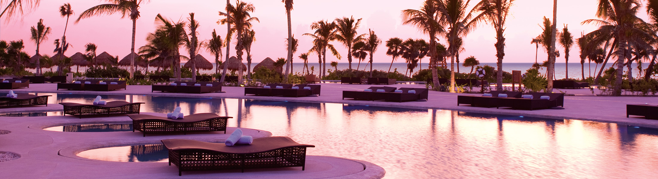 Sunrise over the infinity pool at Secrets Maroma Beach Riviera