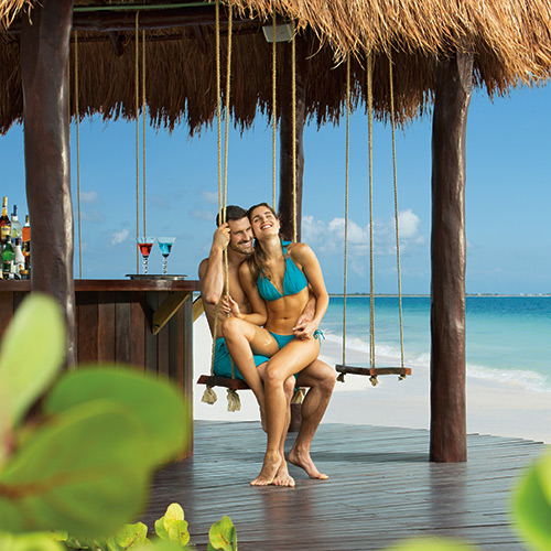 Couple on a swing at a bar on the beach at Secrets Playa Mujeres