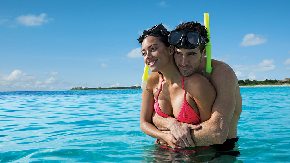 Couple huggin the sea with snorkel equipment at Secrets Akumal