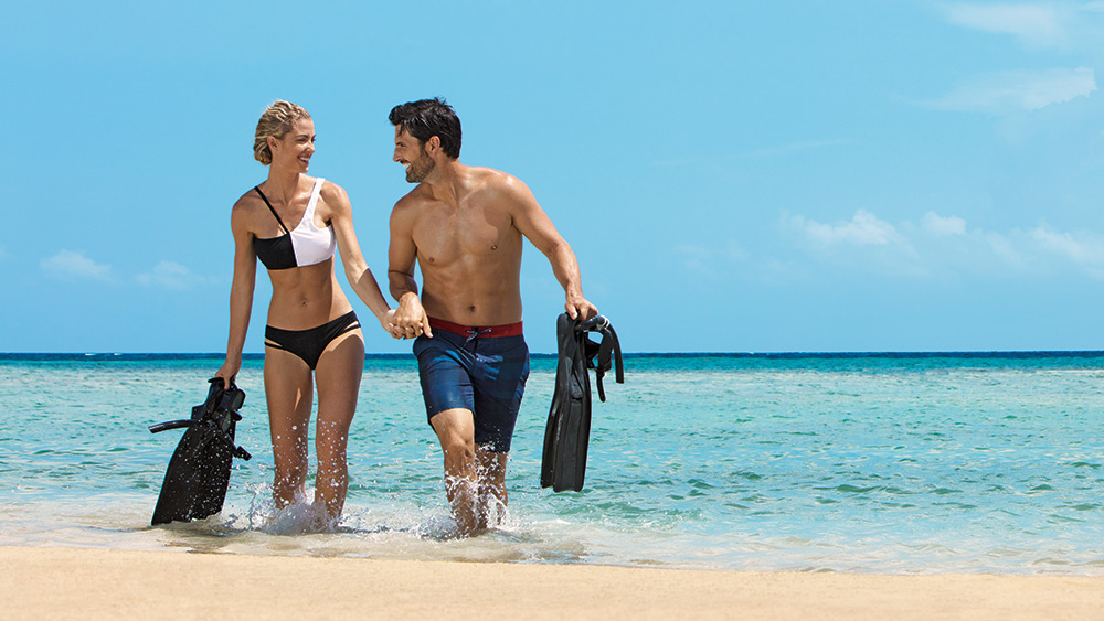 Couple with snorkelling gear in the sea at Zoetry Montego Bay