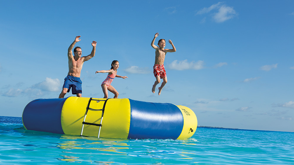 Dad & kids on a trampoline in the sea at Dreams Sands Cancun