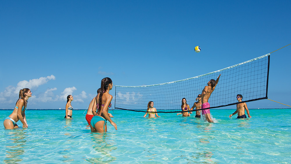 Teens playing volleyball in teh sea at Dreams Sands Cancun
