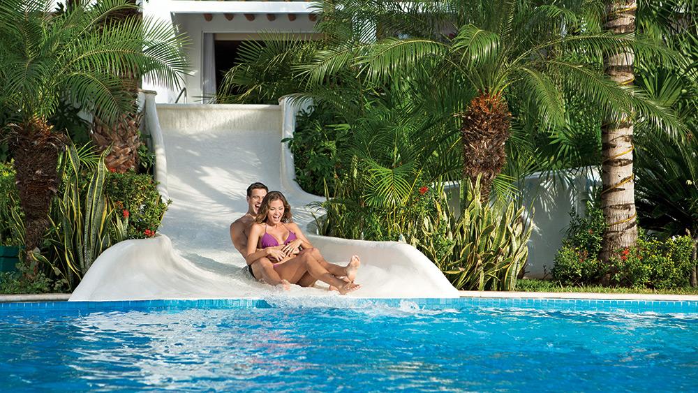 Couple sliding down a water slide at Secrets Aura Cozumel