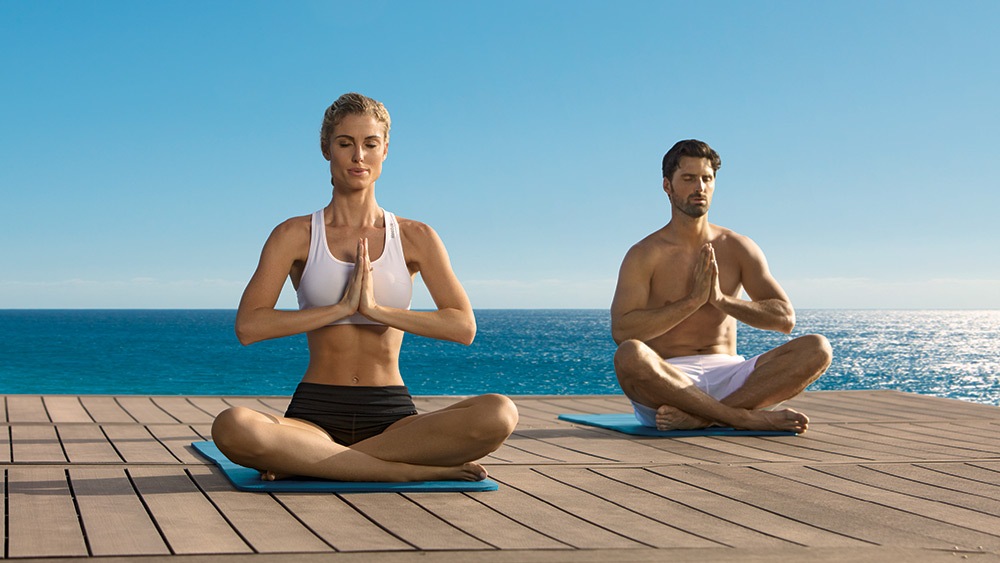 Couple doing yoga on the jetty at Zoetry Montego Bay