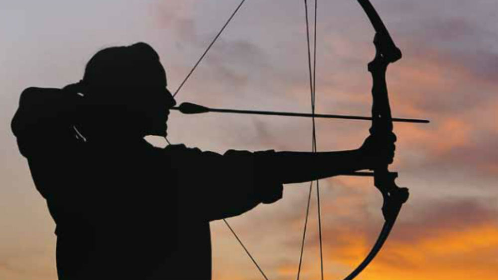 Woman practising archery at sunset at Anantara Qasr Al Sarab Desert Resort