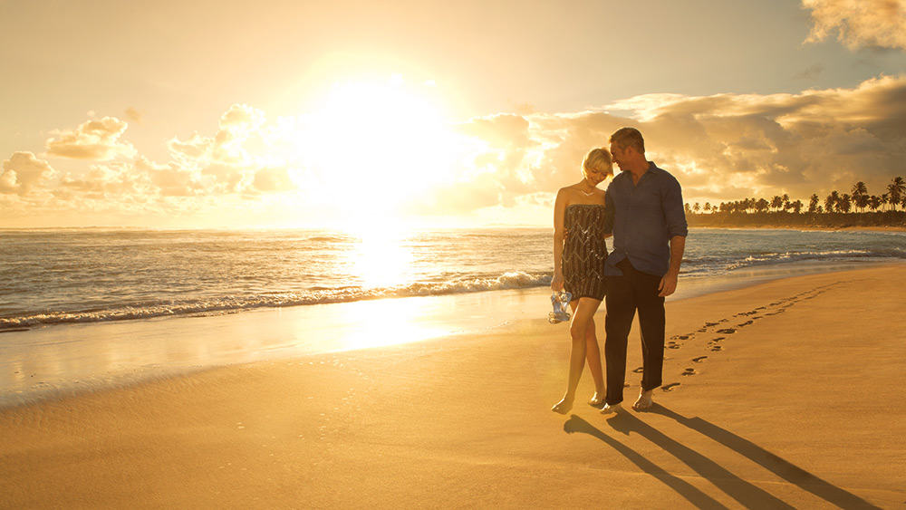 Couple walking on the beach at sunset at Breathless Punta Cana