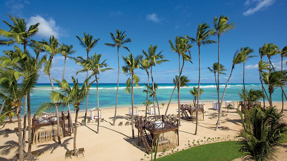 Palm trees and sun loungers on the beach at Breathless Punta Cana