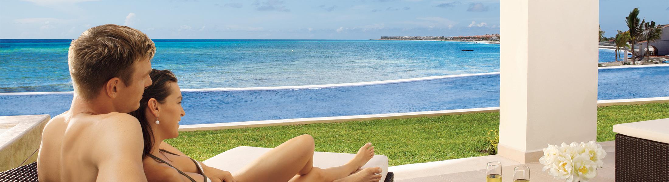 Couple on a sun lounge overlooking the ocean at Secrets Silversands Riviera