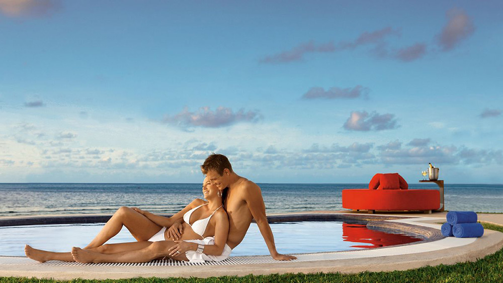 Couple on the edge of a Jacuzzi at Secrets Silversands Riviera