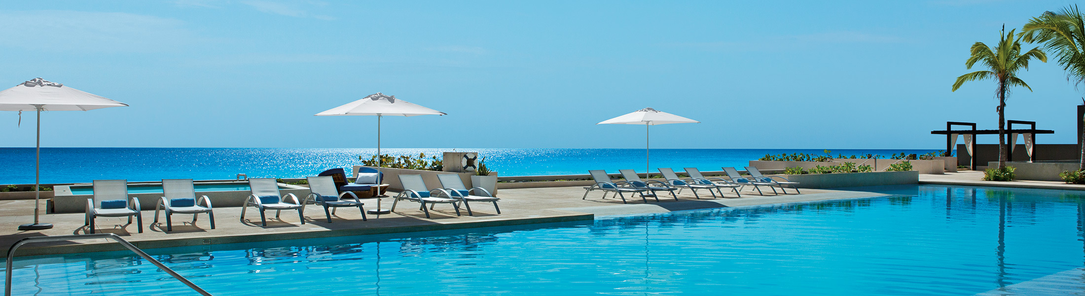 Pool and sun loungers with ocean views at Secrets The Vine