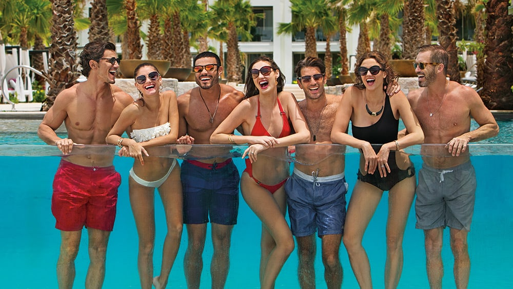Friends against a glass side of a pool at Breathless Riviera Cancun