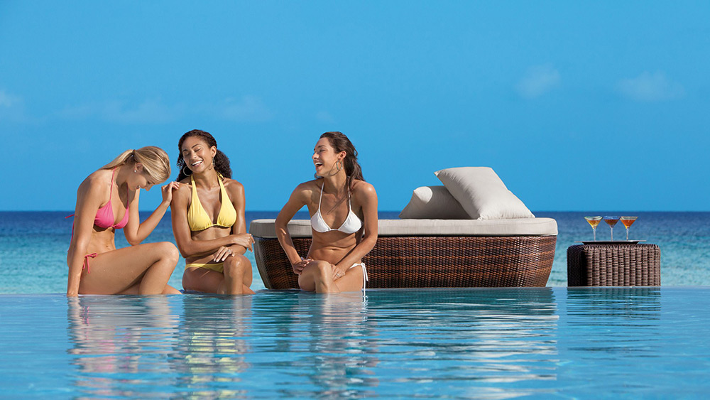Women laughing on the edge of a pool at Secrets St James