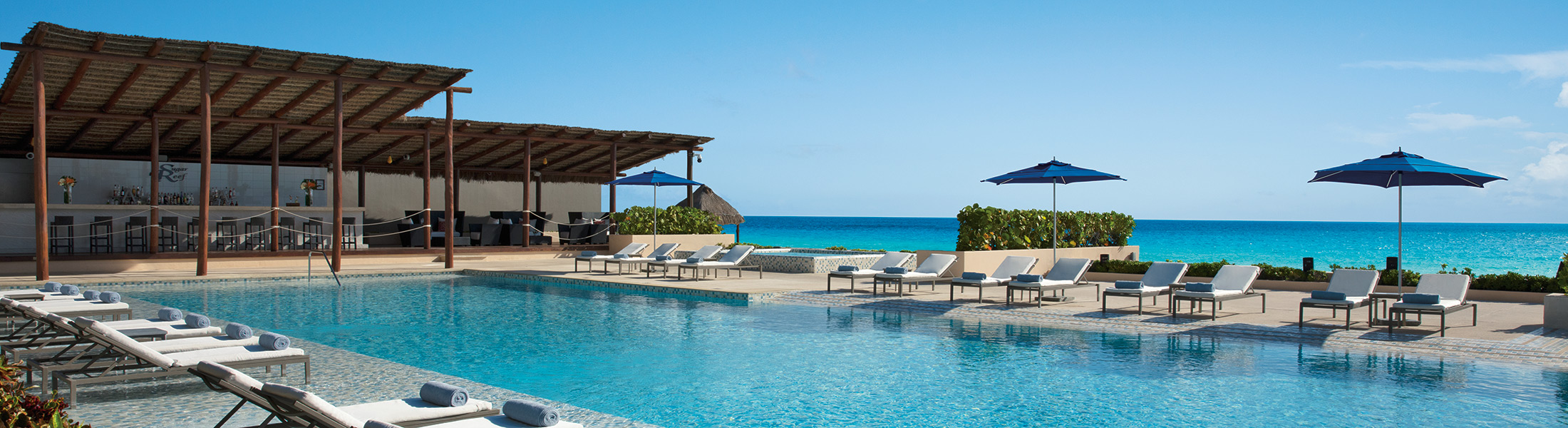 Pool and sun loungers at Secrets The Vine