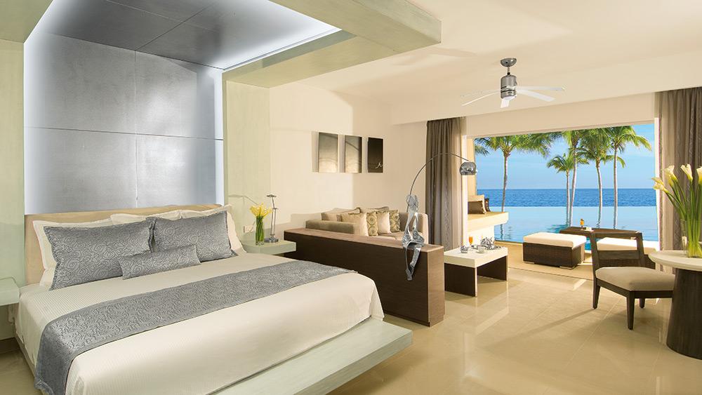 Bedroom of the Preferred Club Junior Suite Oceanfront Swim-Up at Secrets Silversands