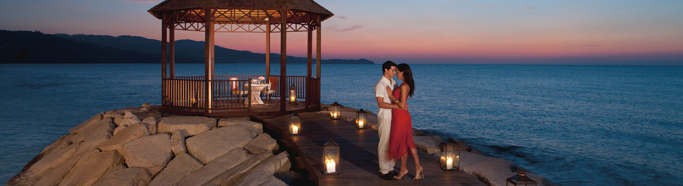 Couple at sunset in a beachfront gazebo dinner at Secrets St James