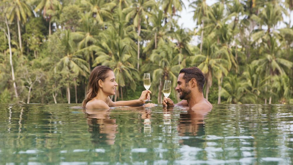 couple relax by Main Pool at the Viceroy Bali