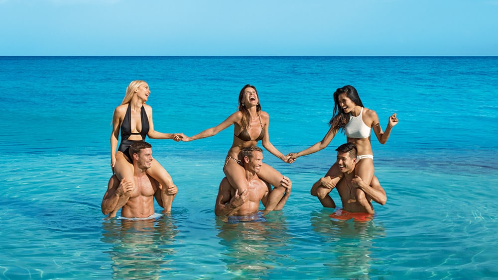Couples giving shoulder rides in the ocean at Breathless Montego Bay