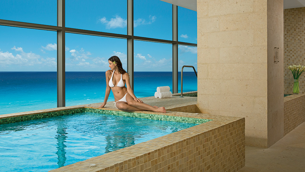 Woman relaxing on the edge of a Jacuzzi in the spa at Secrets The Vine