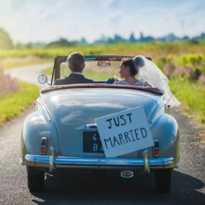 Couple of Newlyweds driving away in a car for their honeymoon