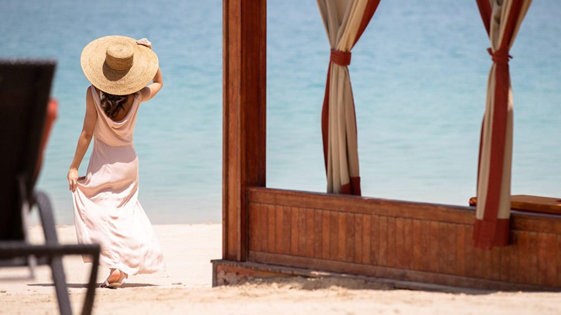 Woman on the beach near a cabana at Jumeirah Zabeel Saray