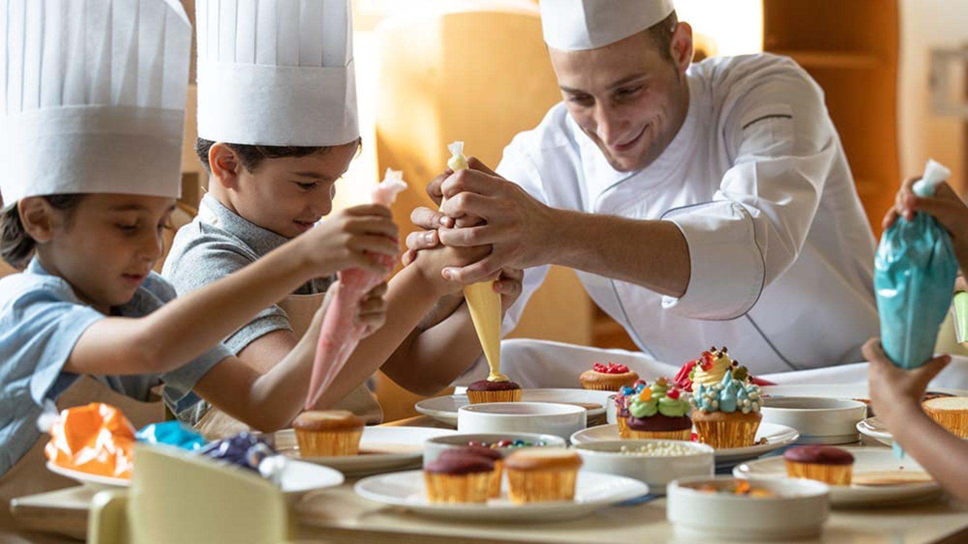 Chef with kids making food at Jumeirah Mina A'Salam