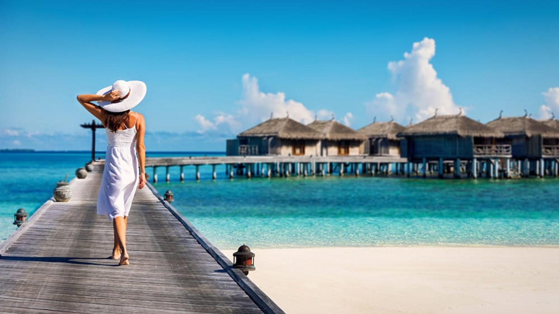 Woman walking on a jetty to overwater villas in the Maldives