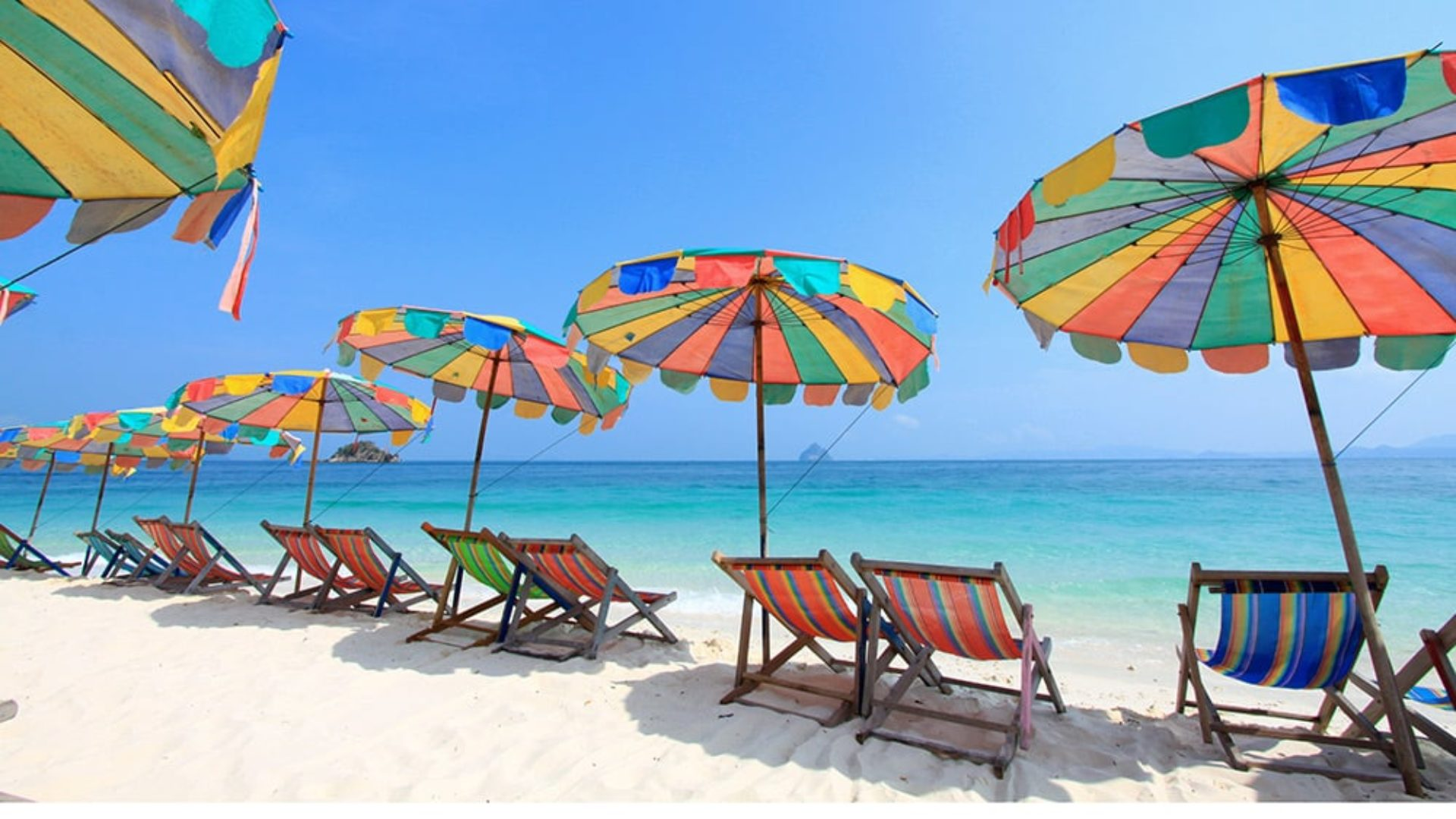 Beach chairs under umbrellas in Phuket on a Thailand Multi-Centre