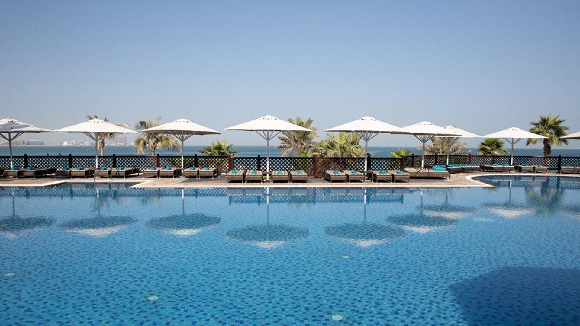 Pool with sun loungers at Jumeirah Mina A'Salam