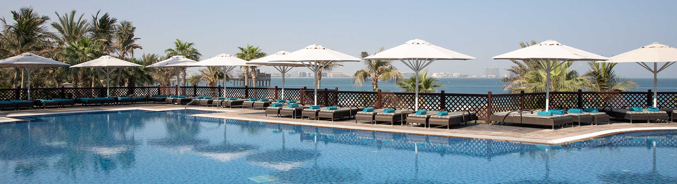 Pool with sun loungers at Jumeirah Mina A'Salam