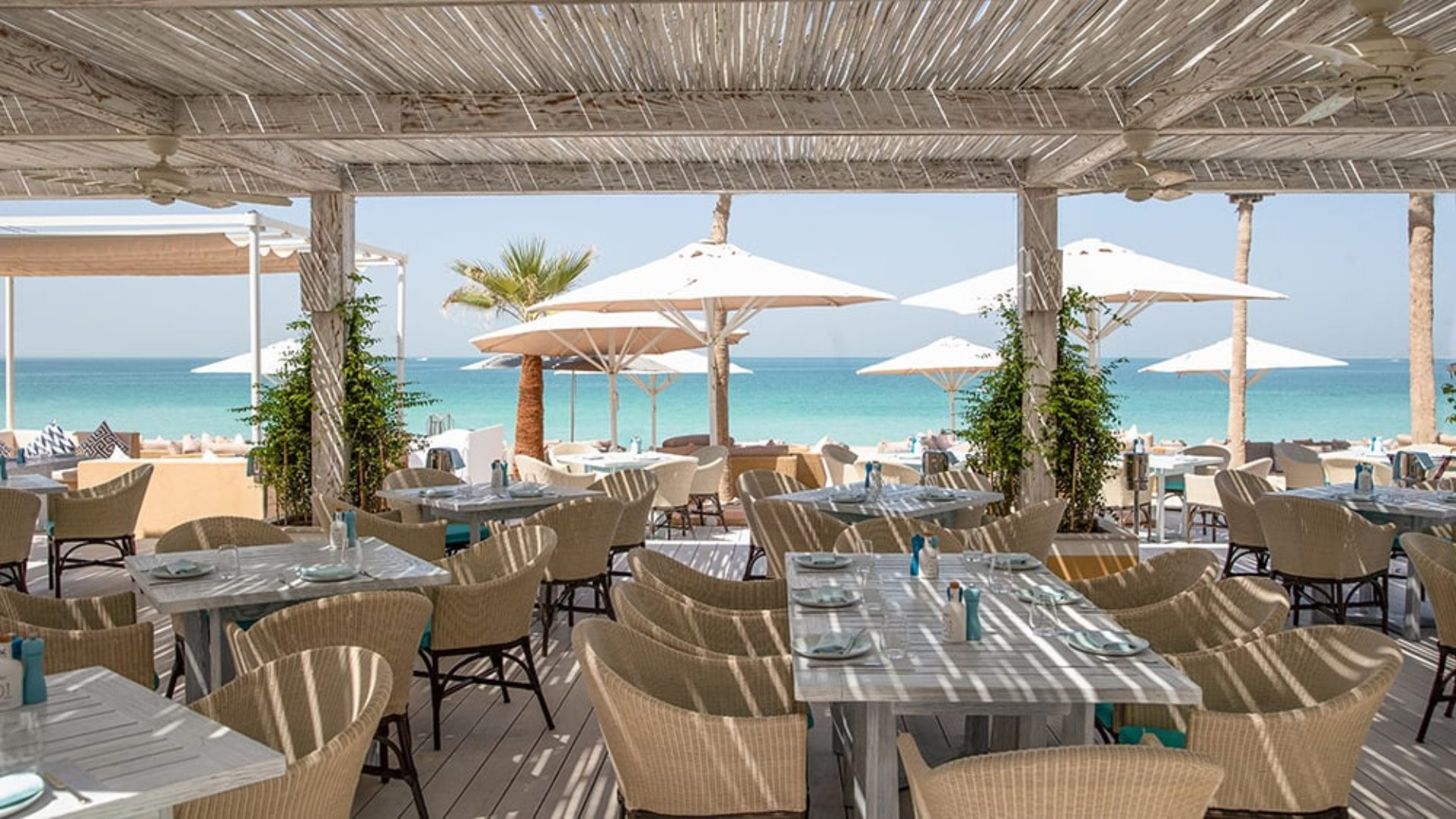 Outdoor terrace dining with beach views at Jumeirah Dar Al Masyaf