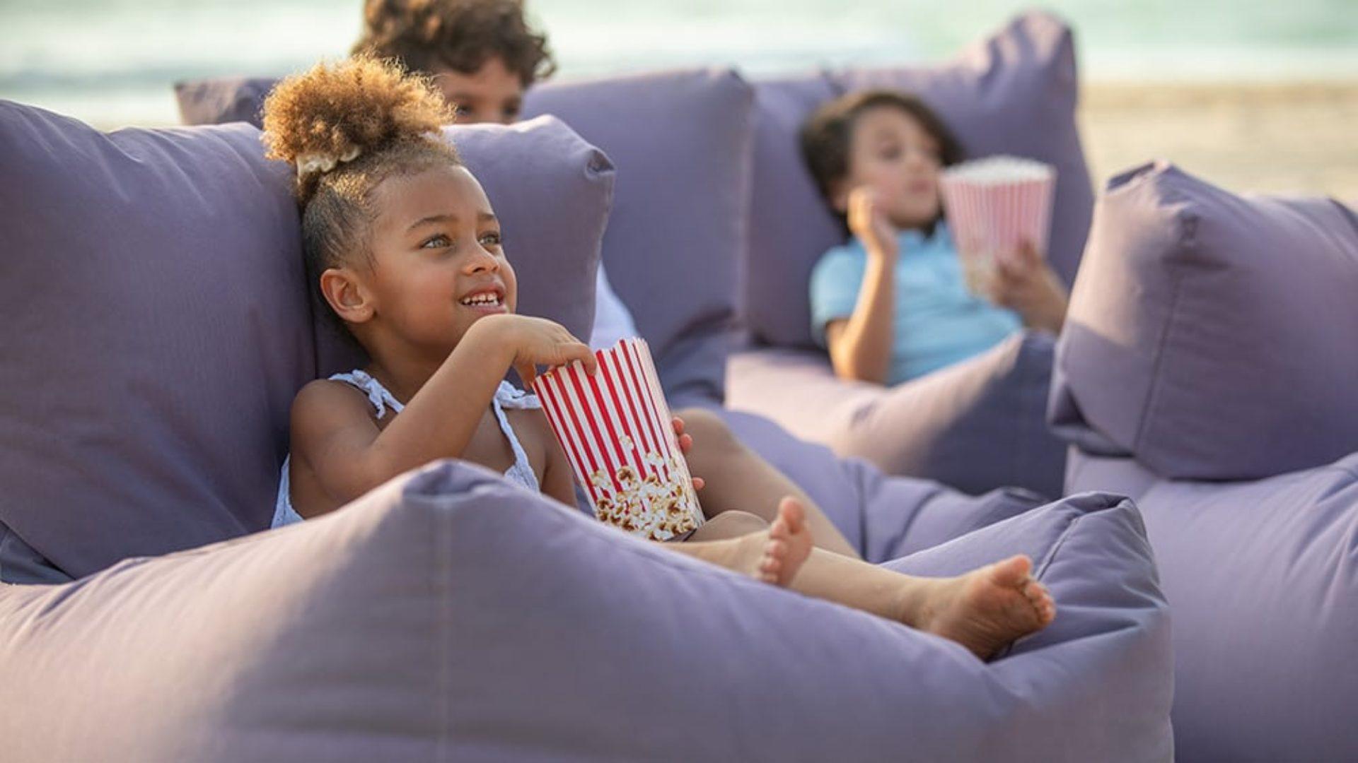 kids eating popcorn at the beach cinema at Jumeirah Beach Hotel