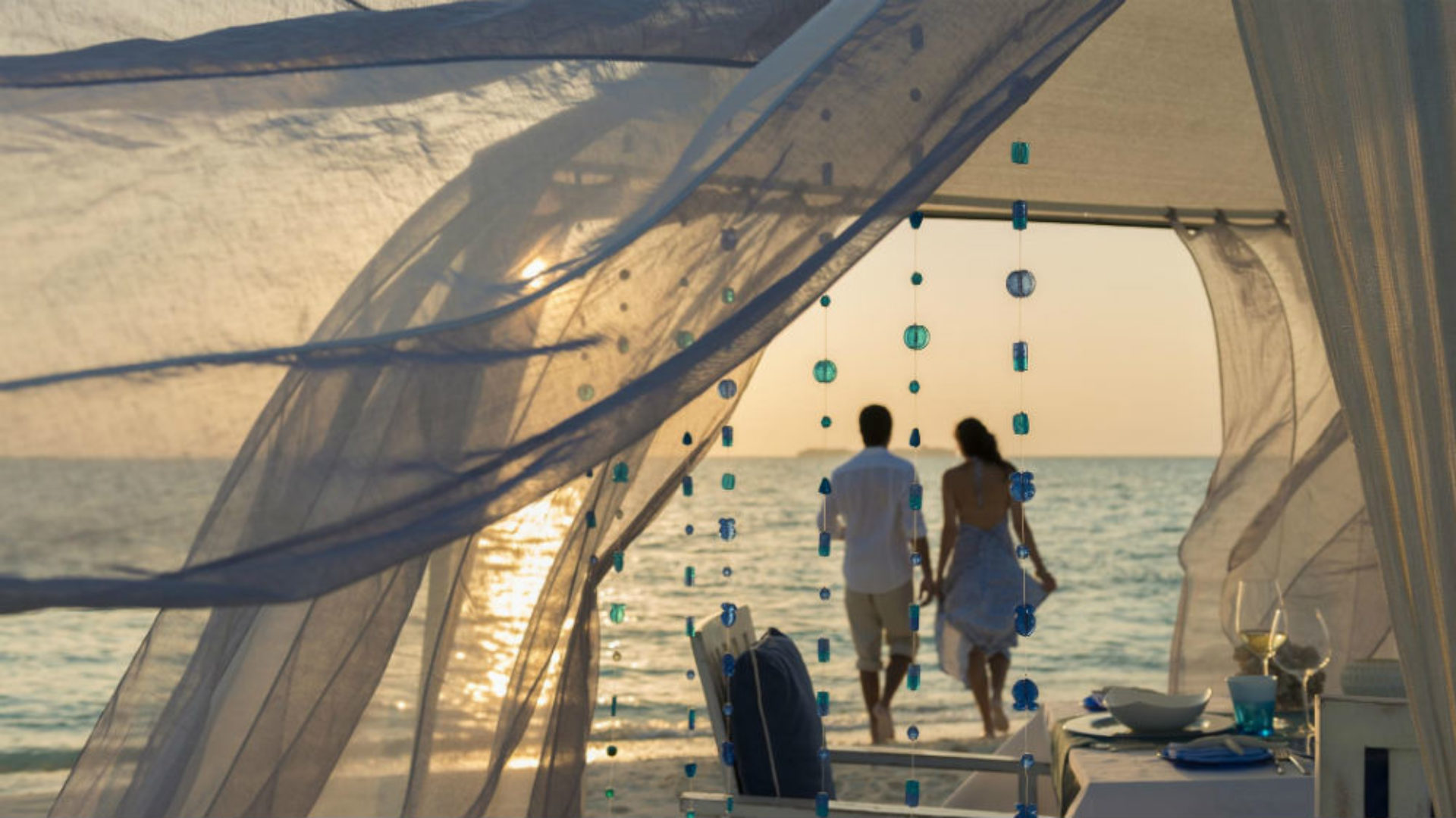 Couple on the beach with a romantic dinner at Nikki Beach Resort & Spa