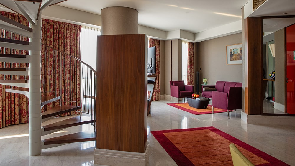 Living room with spiral staircase in the Duplex Suite at Jumeirah Creekside