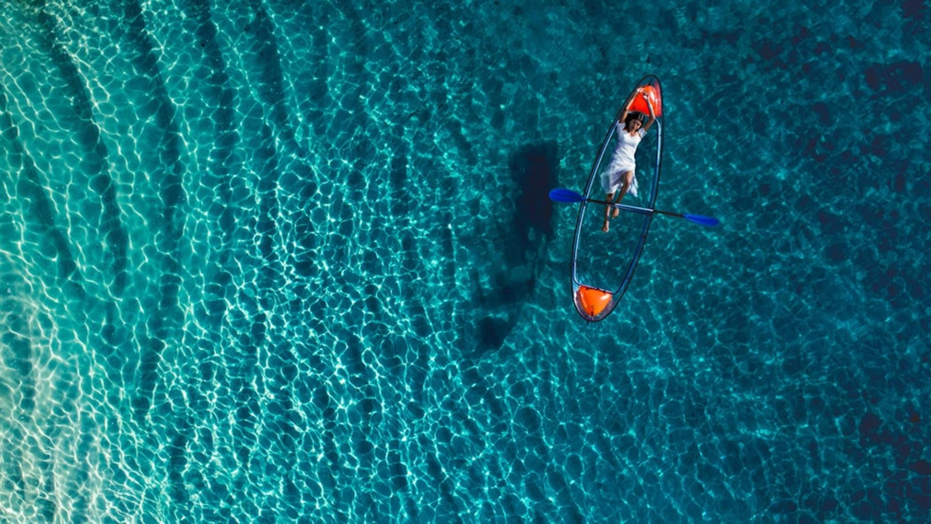 Aerial view of a woman on a glass bottom kayak at Jumeirah Vittaveli