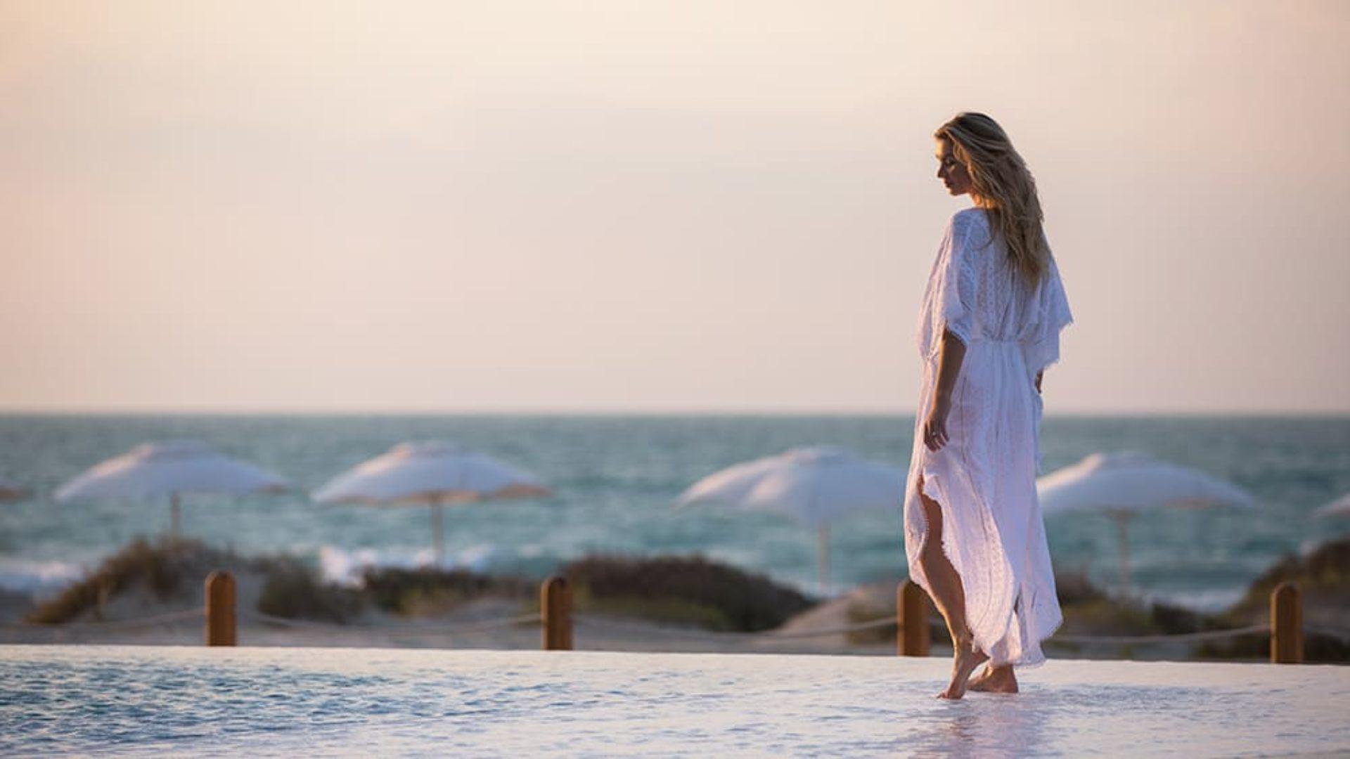 Woman on the edge of an infinity pool at Jumeirah at Saadiyat Island
