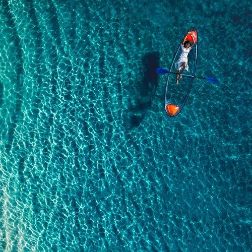 Aerial view of a woman on a glass bottom kayak at Jumeirah Vittaveli