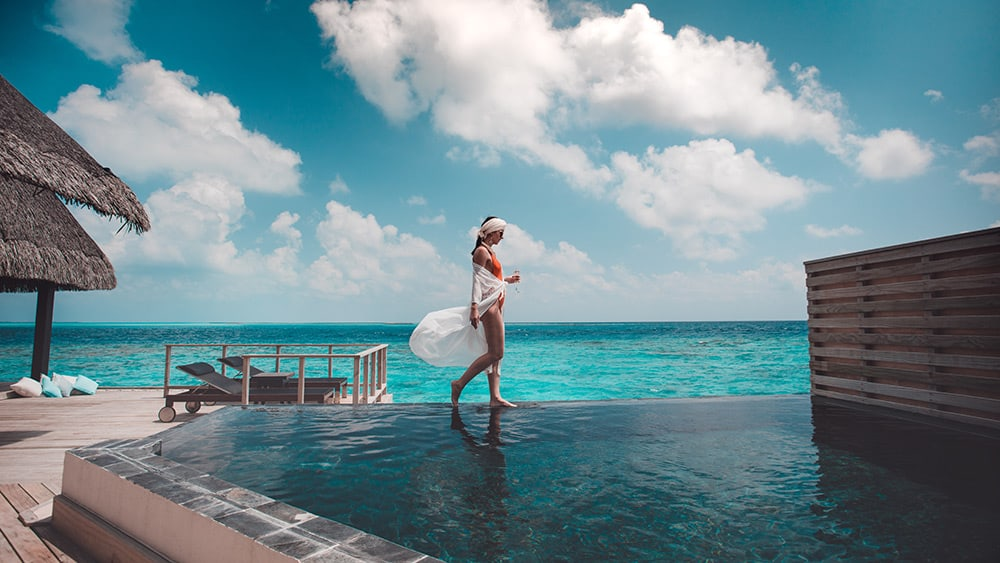 Woman on the edge of an infinity pool in the Private Ocean Retreat with Slide at Jumeirah Vittaveli