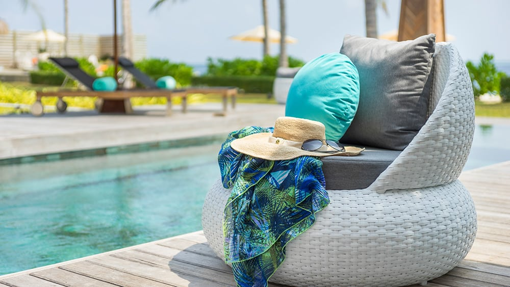 Wicker chair on pool decking in the Royal Residence at Jumeirah Vittaveli