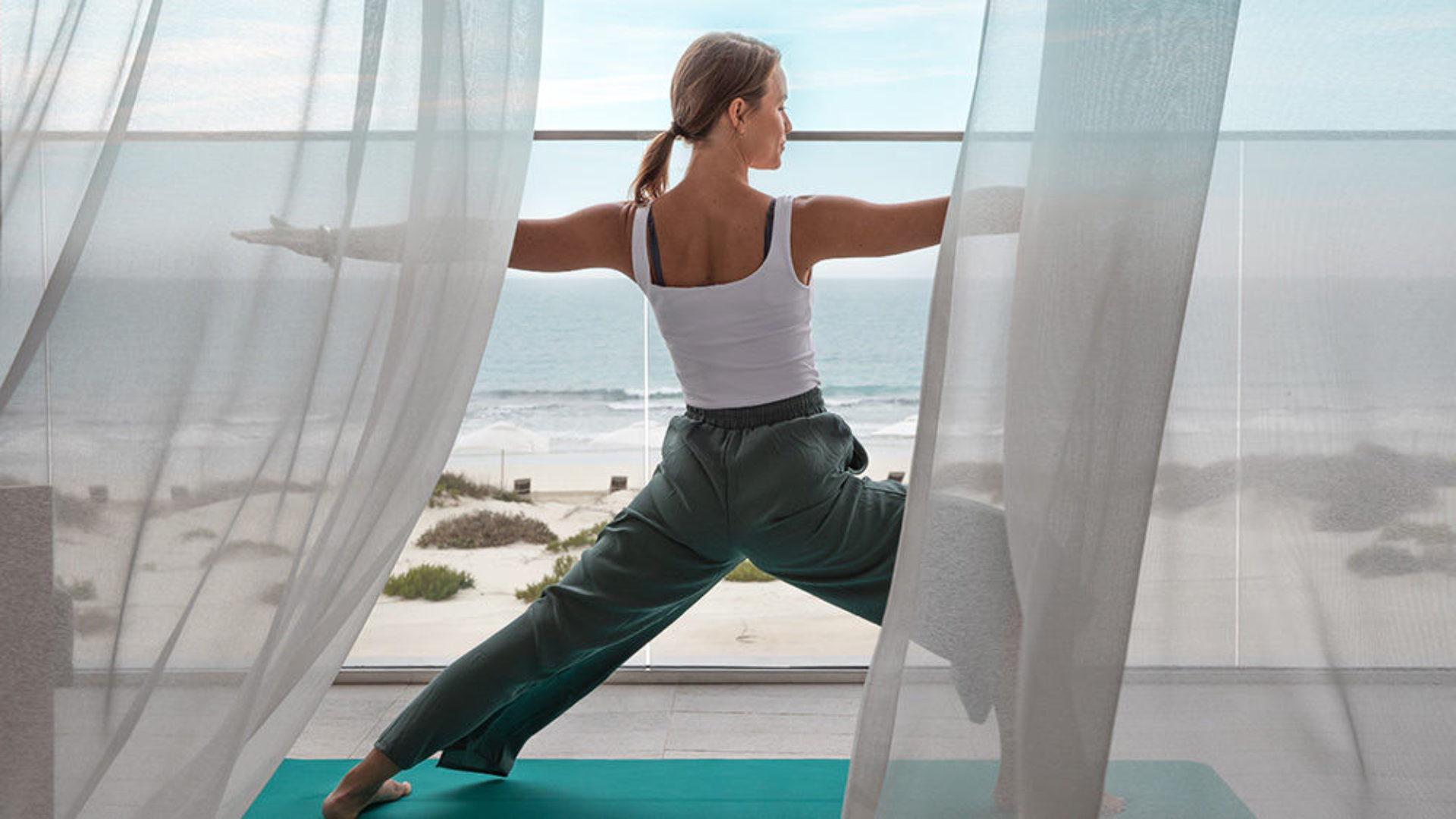 Woman doing yoga on a balcony at Jumeirah at Saadiyat Island